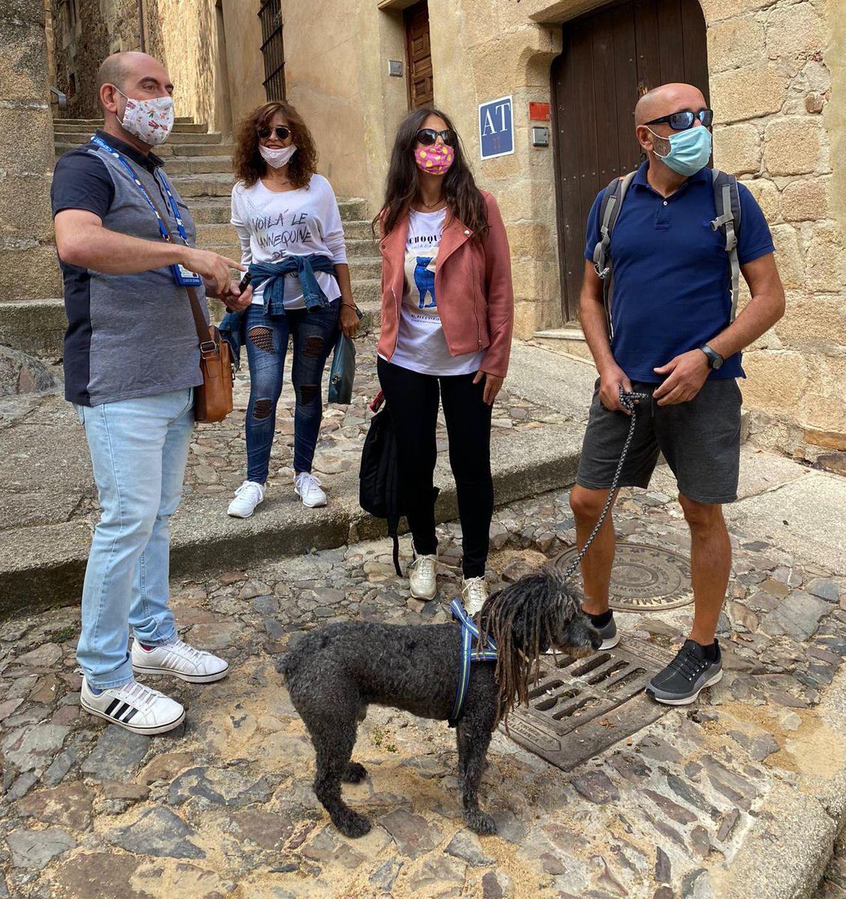 Nuestro compañero el guía de turismo Marco (a la izquierda) dándose un paseo por la ciudad monumental de Cáceres en compañía de una familia con perro. Por cierto, al fondo se ve la entrada de los apartamentos turísticos «Cáceres medieval», igualmente adheridos a la tendencia dog friendly.
